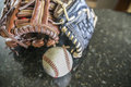 Gloves and ball resting on a table Royalty Free Stock Photo