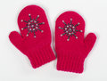 Gloves are a pair of red knitted knit with crystals on gray background Stock Images
