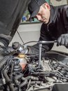 Glow plug replacement auto mechanic replacing plugs in car diesel engine using spark spanner Royalty Free Stock Photography