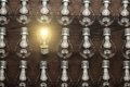 Glowing bulb uniqueness concept on brown wooden table Royalty Free Stock Photos