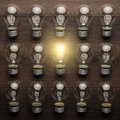 Glowing bulb uniqueness concept on brown woodentable Royalty Free Stock Image
