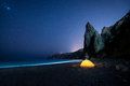 Glowing camping tent on a beautiful sea shore with rocks at night under a starry sky