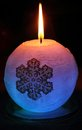 Glowing candle with a diode and snowflake lights up in the dark Stock Photos