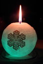 Glowing candle with a diode and snowflake lights up in the dark Royalty Free Stock Images