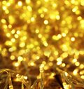 Glowing gold Christmas lights on table, closeup. Bokeh effect Royalty Free Stock Photo