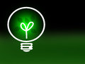 Glowing green light bulb with growing leaves against faded black to green background renewable energy and ecology concept with Stock Images