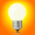 Glowing incandescent light bulb on yellow-orange Royalty Free Stock Photo