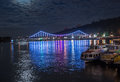 Glowing multicoloured city bridge above river at night and boats quay Stock Image