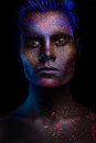 Glowing neon makeup with dramatic look in his eyes.