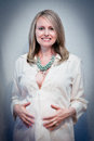 Glowing pregnant woman a beautiful wearing an embroidered white shirt and long beaded necklace Stock Photo