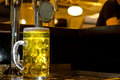 Glowing tankard of golden draught beer large glass standing on a wooden counter in a bar alongside a row stainless steel taps Royalty Free Stock Photo