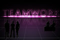 Glowing teamwork word on grid with a three dimensional design and reflection silhouettes of men and women teams purples and black Stock Images