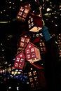 Glowing toy houses on christmas tree in dark Royalty Free Stock Images