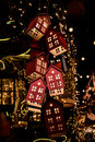 Glowing toy houses on christmas tree in dark Stock Photography
