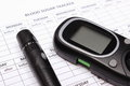 Glucometer and lancet device on empty medical forms for diabetes Royalty Free Stock Photo