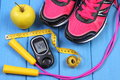 Glucometer, sport shoes, fresh apple and accessories for fitness on blue boards Royalty Free Stock Photo