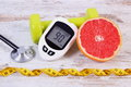 Glucometer, stethoscope, fresh grapefruit and dumbbells for fitness, diabetes, healthy lifestyles