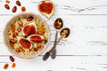 Gluten free amaranth and quinoa porridge breakfast bowl with figs, caramelized almonds, raisins and honey over rustic white table. Royalty Free Stock Photo