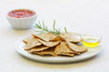 Gluten free rosemary olive oil crackers and with salsa on white plate in horizontal format Stock Photos