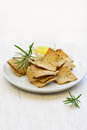 Gluten free rosemary olive oil crackers and on white plate in horizontal format Royalty Free Stock Images