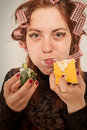 Gluttonous woman young hungry eating pie and cucumber Royalty Free Stock Image