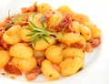 Gnocchi with tomatoes bacon and onion on the white plate Stock Image