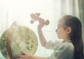 Go on an adventure cute child girl playing with toy airplane and globe Stock Images