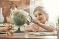 Go on an adventure happy cute child preparing for the journey pretty girl study the globe and choose a route of travel Royalty Free Stock Photos
