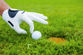 Go in close up of male hand golf glove touching golf ball laying near the hole Stock Images