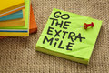 Go the extra mile motivational reminder or procrastination concept handwriting on sticky note handwriting on sticky note Royalty Free Stock Photo