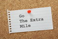 Go the extra mile phrase typed on a piece of lined note paper and pinned to a cork notice board Royalty Free Stock Photography