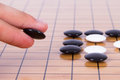 Go game close up view of hand playing black and white stone pieces on chinese board Stock Images