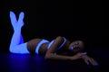 Go-go girl lying under ultaviolet uv-light Stock Images