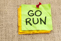 Go run reminder or fitness concept handwriting on green sticky note Stock Images