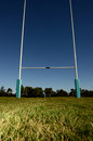 Goal posts on a sporting field situated set against blue sky in the background and grass in the foreground Royalty Free Stock Photo