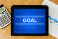 Goal word on digital tablet with calculator and financial graph Royalty Free Stock Image