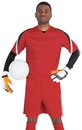 Goalkeeper in red holding the ball on white background Royalty Free Stock Photo