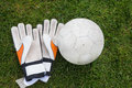 Goalkeeping gloves and football on pitch Royalty Free Stock Photo