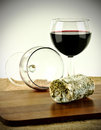 Goats cheese and wine a closeup of mature a full glass of red a finished glass on a wooden board Stock Images