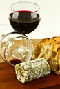 Goats cheese and wine a closeup of mature a full glass of red a finished glass on a wooden board Royalty Free Stock Images