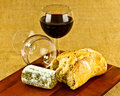 Goats cheese and wine a closeup of mature a full glass of red a finished glass on a wooden board Stock Photography