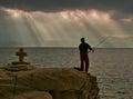 Gods rays, cross and fisherman Royalty Free Stock Photo