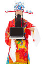 God of wealth holding a laptop over white background Royalty Free Stock Images
