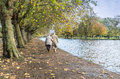 Going home elderly couple walking by the river bank on a cold day in autumn Royalty Free Stock Photo