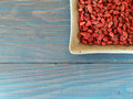 Goji berries sweet organic in a bowl on a blue wooden board Royalty Free Stock Photos