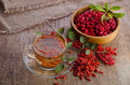 Goji fresh antioxidant tea in glass cup and barberries in wooden desk Stock Photography