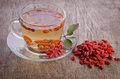 Goji fresh antioxidant tea in glass cup and barberries in wooden desk Royalty Free Stock Image