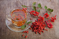 Goji fresh antioxidant tea in glass cup and barberries on wooden desk Stock Images