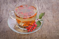 Goji fresh antioxidant tea in glass cup and barberries in wooden desk studio photo Stock Images
