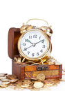 Gold alarm clock lay on money in a wooden chest Stock Photography